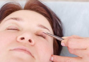 Female surgeon applies a bandage to the female patient's eyelids after a blepharoplasty operation. Close up portrait